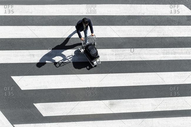 Man on zebra crossing pushing baggage cart- top view