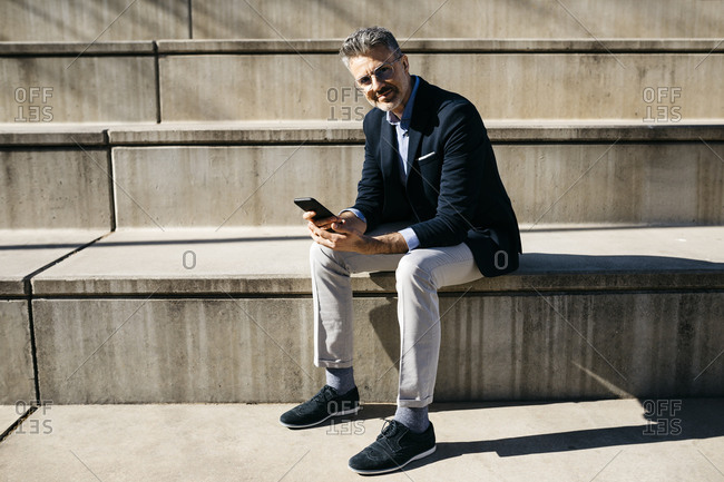 Portrait of confident gray-haired businessman sitting on stairs holding cell phone