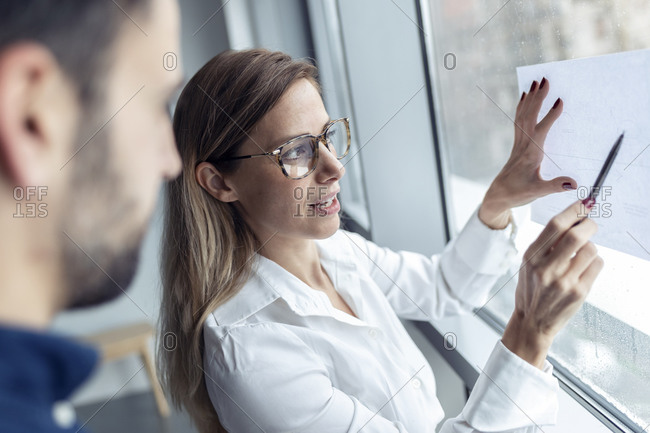 Businesswoman holding sheet of paper on window- drawing chart with colleague watching