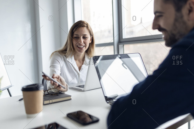 Businesswoman showing smartphone message to colleague- sitting in office