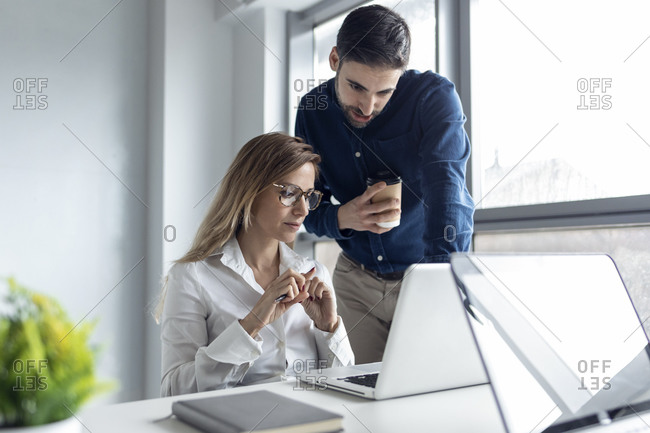 Businesswoman sitting at desk- discussing work with her colleague