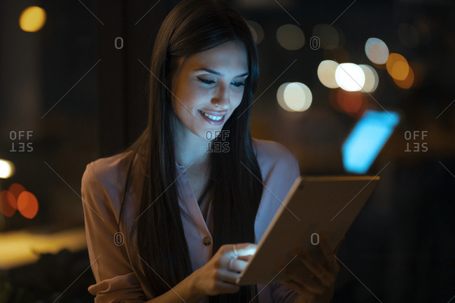 Portrait of smiling young woman using digital tablet in office
