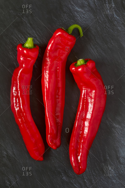 Germany- Three red chili peppers on black stone surface