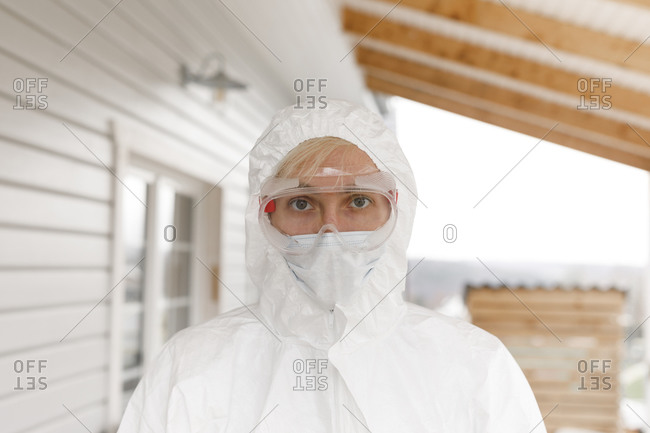 Man in protective clothing- standing in front of house