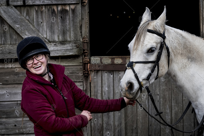 Young woman standing outside stable, holding white Cob horse by it's reins.