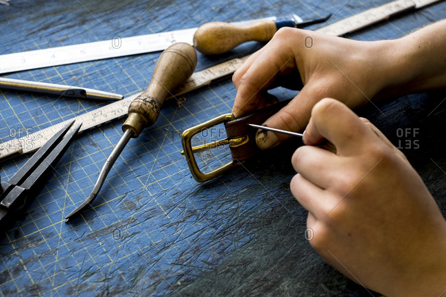 High angle close up of person working in saddler's workshop, attaching buckle to leather strap.