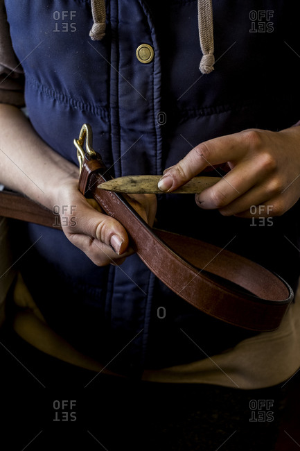 Close up of person in saddler's workshop holding leather strap.