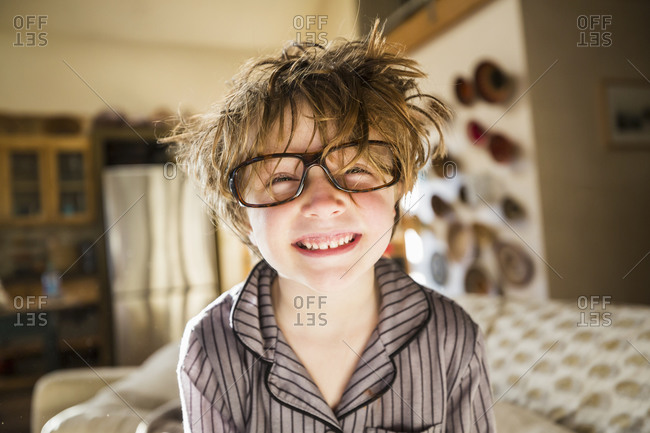 Portrait of a six year old boy with disheveled hair and oversized glasses waking up.