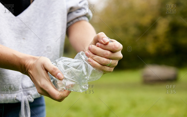 Woman stuffing soft waste plastics into large plastic bottle to make an ecobrick for use as a building block
