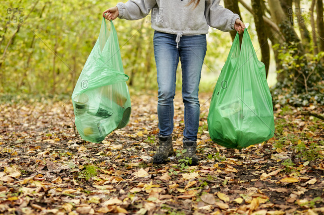 Woman walking in woodland holding two plastic bags full of rubbish