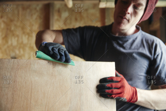 Carpenter sanding down wood for a smooth finish
