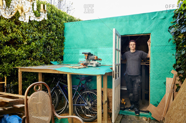 Man standing in doorway of garden shed used for carpentry