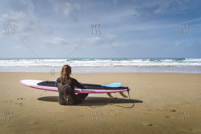 Female surfer sitting on the shoreline holding surfboard