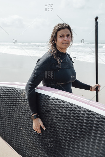 Female surfer standing on the shoreline holding her surfboard