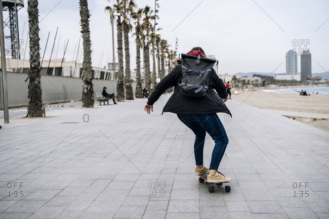 Young woman on skateboard by the beach