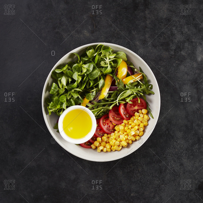 Bowl with fresh corn- paprika- corn salad- tomatoes and olive oil