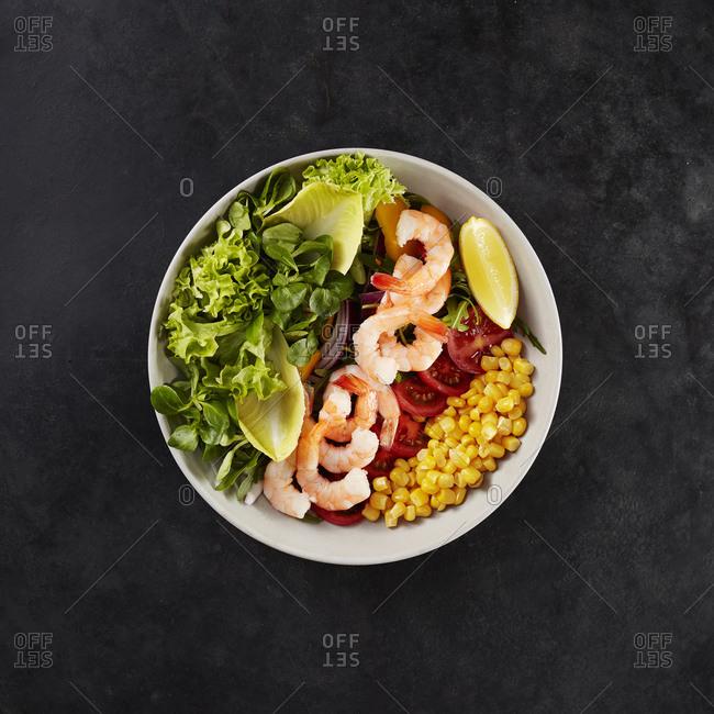 Bowl with fresh corn- tomatoes- lemon- shrimps- chicory and lollo bionda lettuce