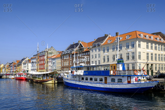 June 11, 2019: Denmark- Copenhagen- Boats moored along Nyhavn canal with colorful townhouses in background