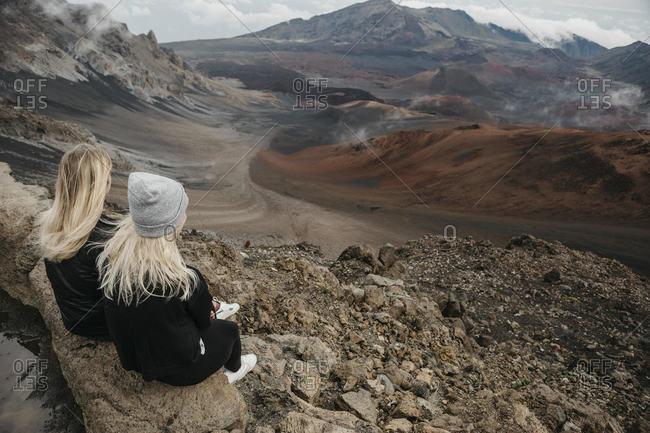 Rear view of female friends sitting at Haleakala Crater- Maui- Hawaii- USA