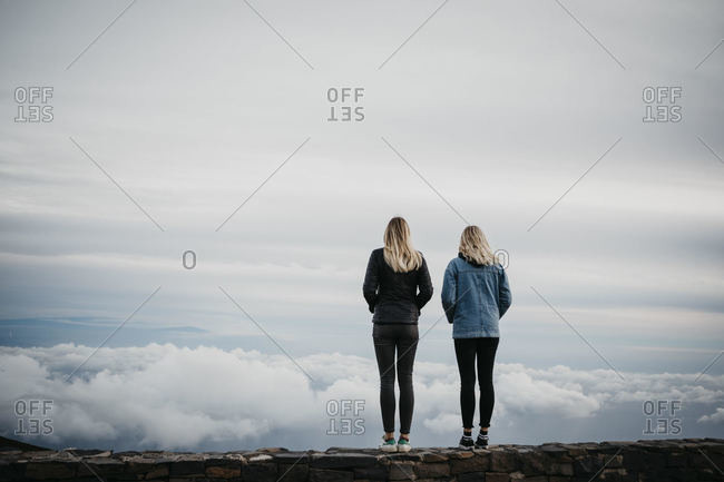 Rear view of female friends looking at idyllic cloudscape while standing at Haleakala Volcano- Hawaii- Maui- USA