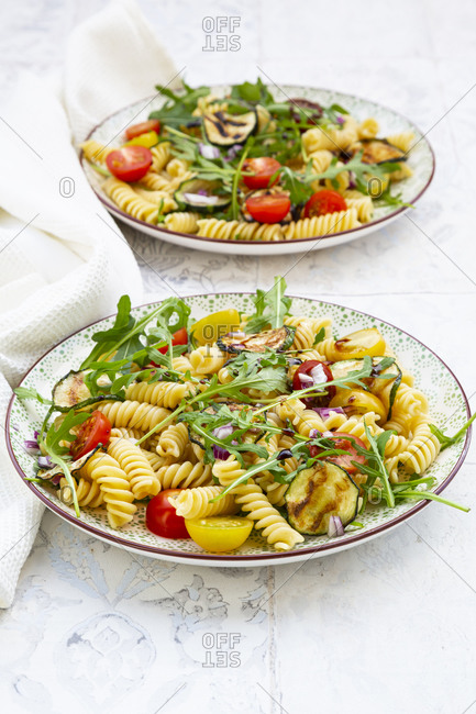 Two plates of vegetarian pasta salad with grilled zucchini- tomatoes- arugula- red onions and balsamic vinegar
