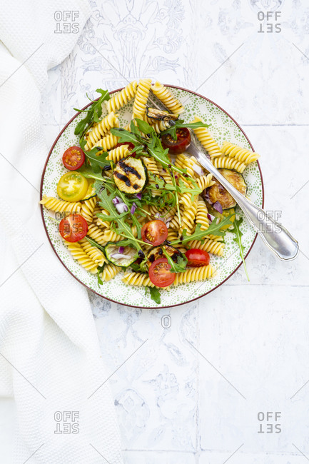 Plate of vegetarian pasta salad with grilled zucchini- tomatoes- arugula- red onions and balsamic vinegar