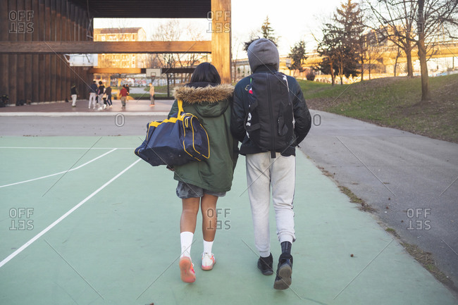 Rear view of young couple walking on sports field