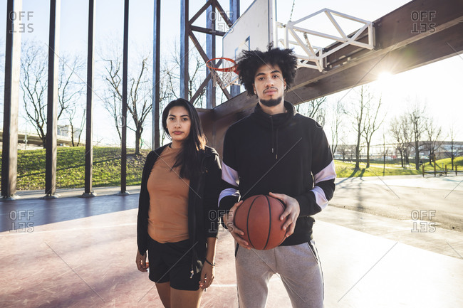 Portrait of young man and woman standing on basketball court in backlight