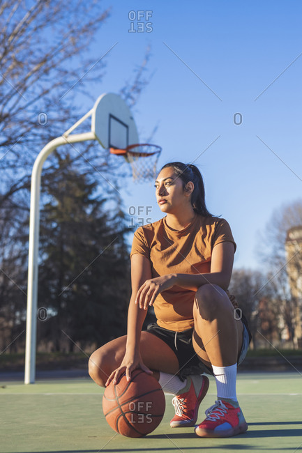 Female basketball player crouching on court