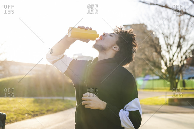 Young sportive man drinking from reusable water bottle
