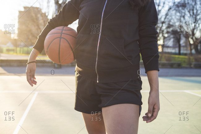 Mid-section of female basketball player on court