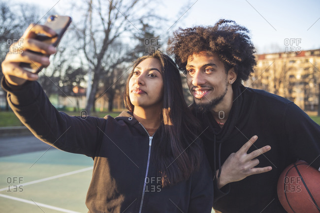 Young sportive couple taking a selfie at sunset