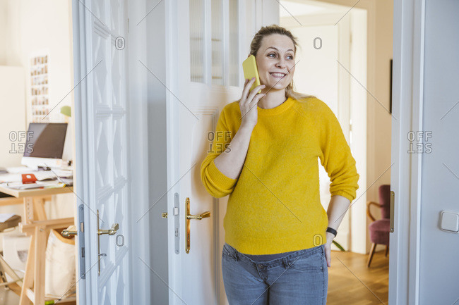 Pregnant woman at home talking on the phone