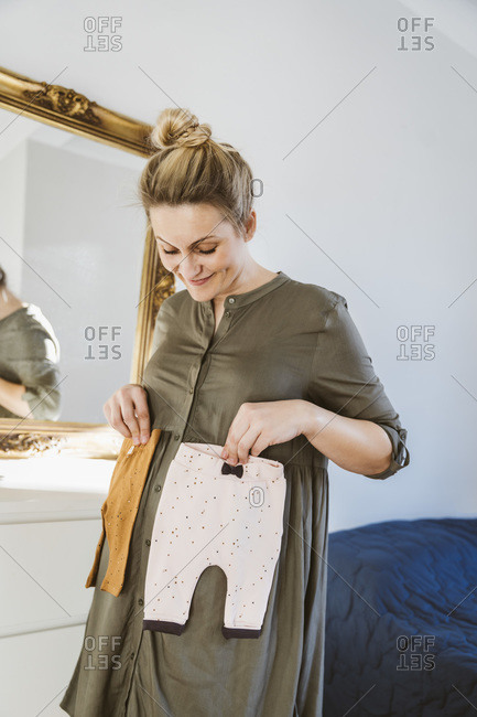 Pregnant woman holding baby clothes at home