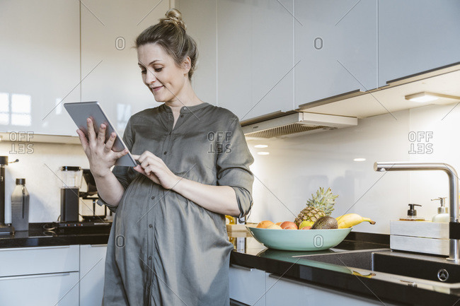 Pregnant woman using tablet in kitchen at home