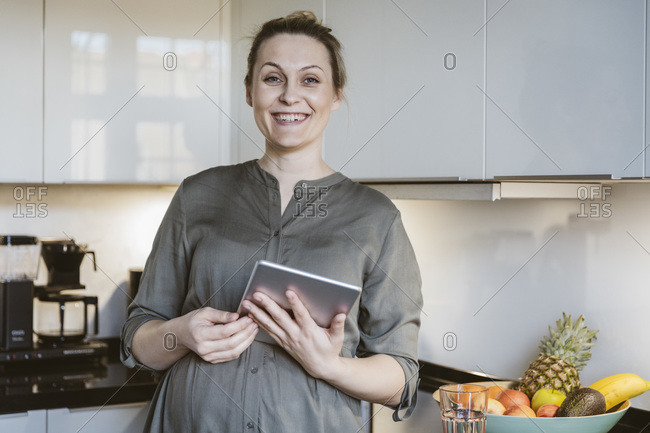 Portrait of happy pregnant woman holding tablet in kitchen at home