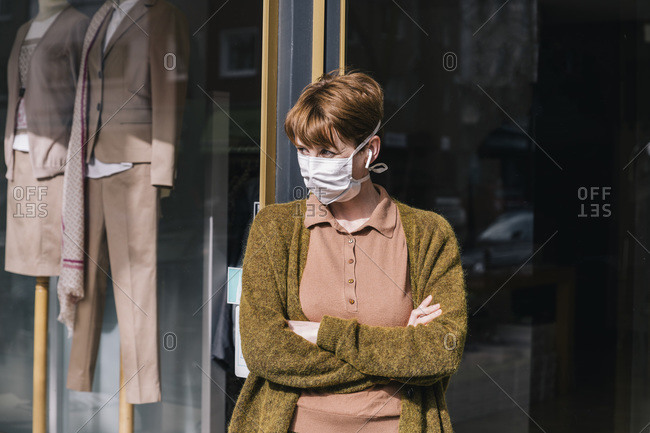 Woman wearing mask standing in front of her closed clothing store
