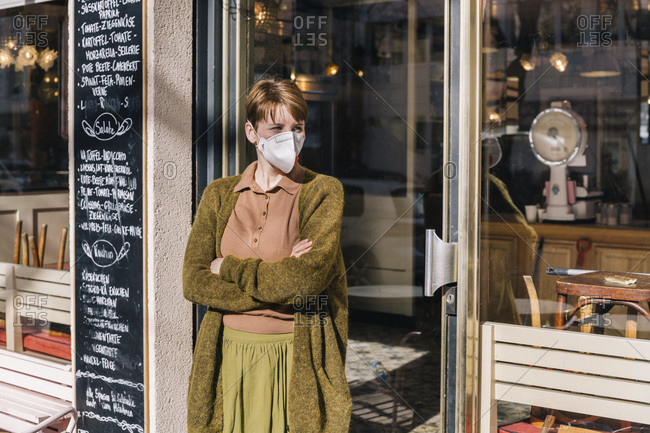 Woman wearing mask standing in front of her closed restaurant