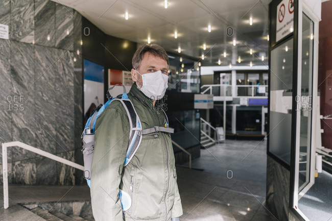 Man with mask standing in entrance of shut down shopping center