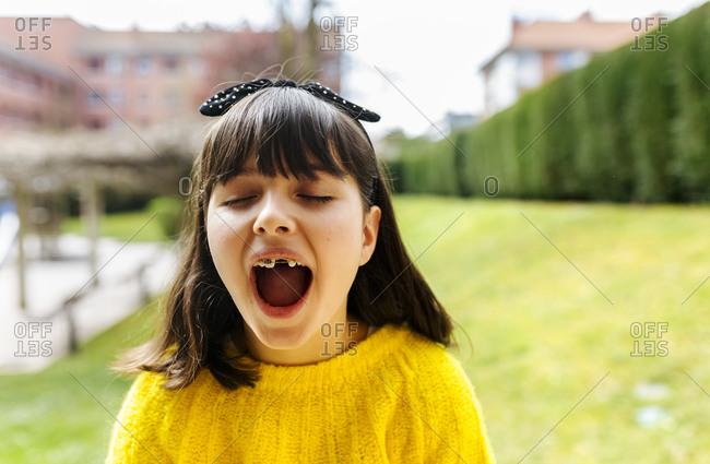 Portrait of a girl with braces on her teeth outdoors