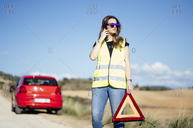 Woman having a breakdown in the countryside talking on the phone