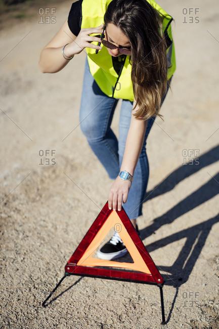 Woman having a breakdown posting warning triangle