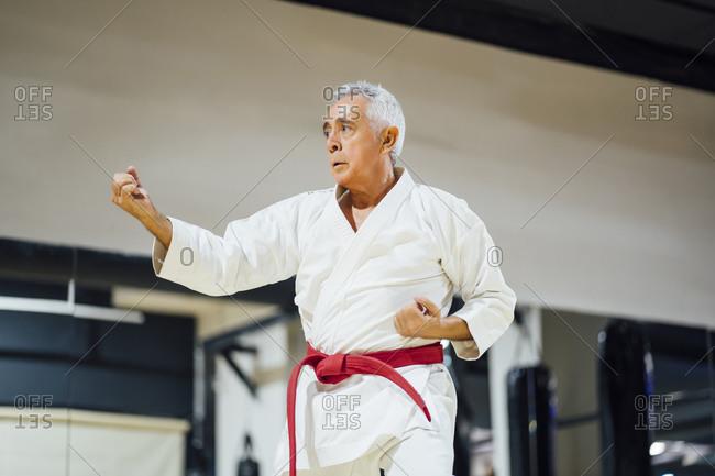 Senior man practicing karate in gym