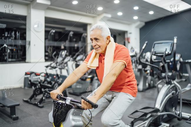 Senior man practicing at exercise machine in gym
