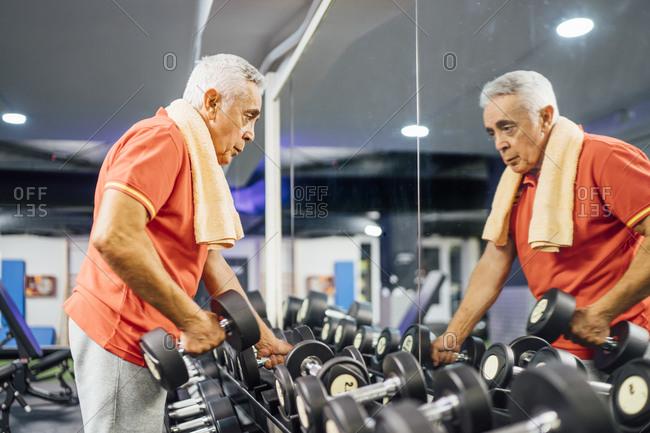 Senior man taking dumbbells from rack in gym