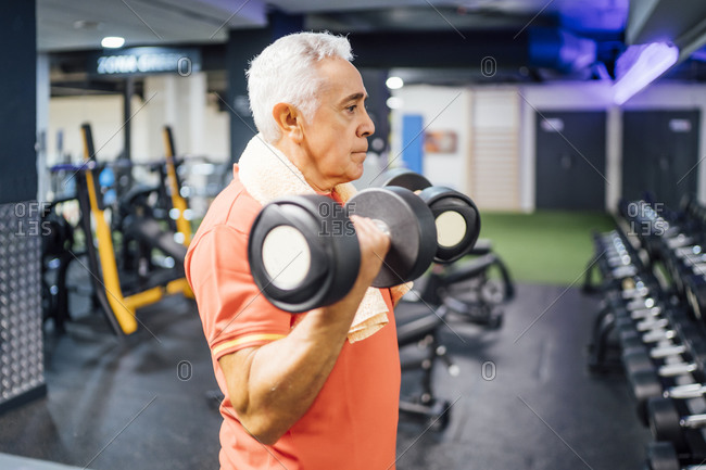 Senior man lifting dumbbells in gym
