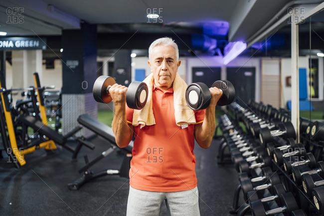 Portrait of senior man lifting dumbbells in gym