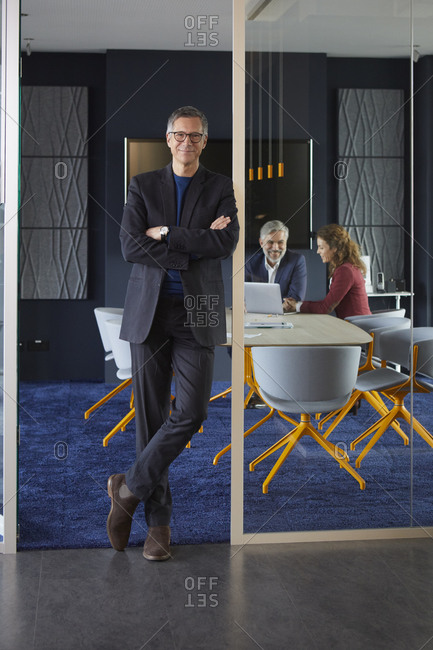 Portrait of confident businessman in office with colleagues in background
