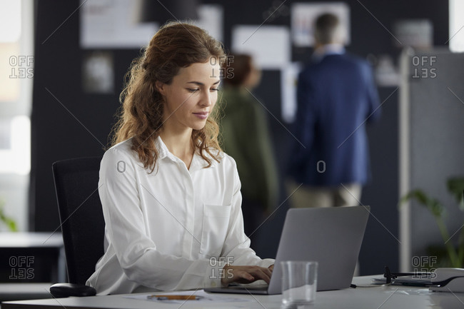 Businesswoman using laptop at desk in office with colleagues in background