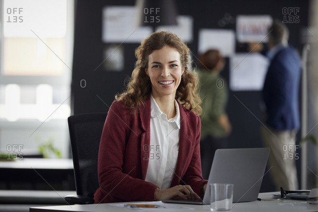 Portrait of smiling businesswoman using laptop at desk in office with colleagues in background